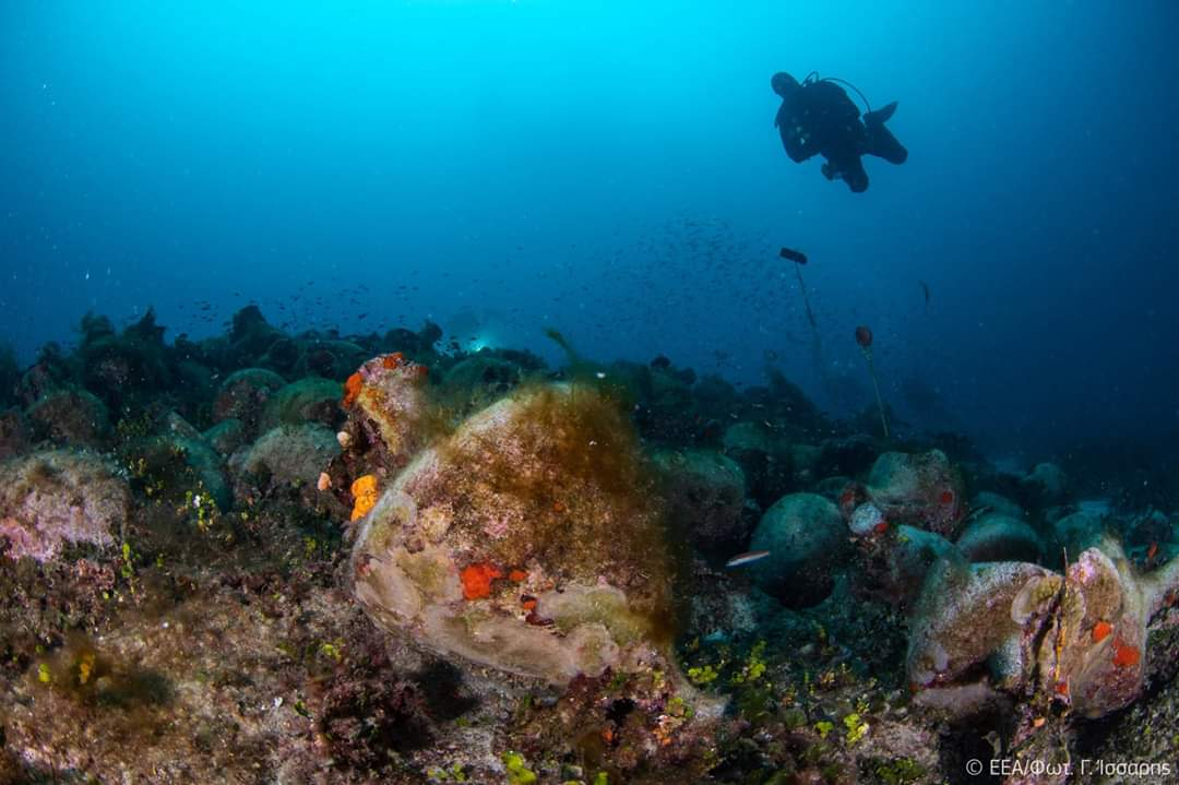diver approaches an amphorae to Peristera Shipwreck
