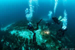 Scuba divers approaching Peristera wreck's jars in display